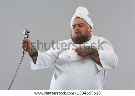 Bath dancer. Isolated on the grey background positive fat man looking funny while closing his eyes and dancing with shower head and puff #1304665618