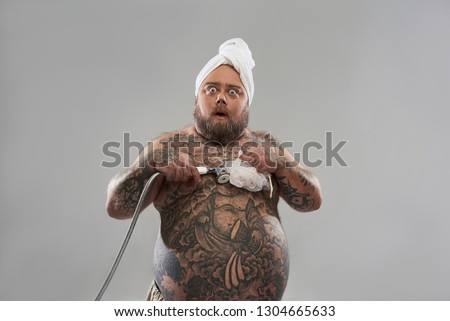 Waist up of fat tattooed man isolated on the grey background putting shower head on his belly and making surprised face #1304665633
