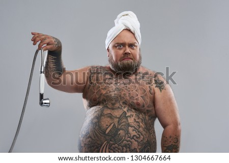 Tattooed fat man with towel on his head standing isolated on the grey background and frowning while holding shower hose with two fingers #1304667664