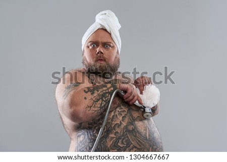 Waist up of funny surprised fat man standing isolated on the grey background and pressing shower head with shower puff to his tattooed belly #1304667667