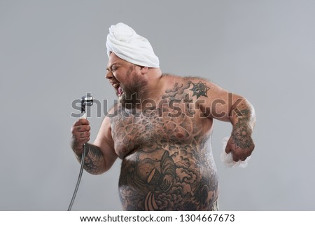 Talented funny fat man closing his eyes and singing with shower head in one hand while standing isolated on the grey background #1304667673