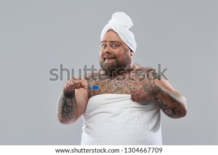 Waist up on the grey background of funny fat man wearing white towels on his head and body and smiling while holding a blue toothbrush #1304667709