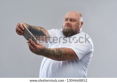 Fat bearded man with tattooed arms standing isolated on the grey background and making funny faces while holding modern smartphone #1304668852