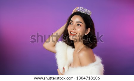 Portrait of Miss Pageant Beauty Contest in white fur Evening dress light Diamond Crown, LGBT transgender Asian Woman fashion make up black hair style, studio lighting gradient shade purple background #1304718106