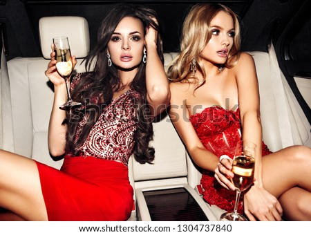 Sexy woman couple in the car. Hollywood star. Fashionable pair of elegant people at night city street. #1304737840