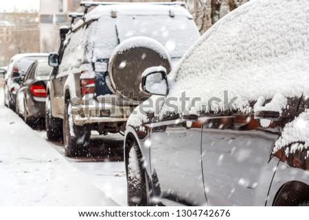 Snow on cars after snowfall. Winter urban scene #1304742676