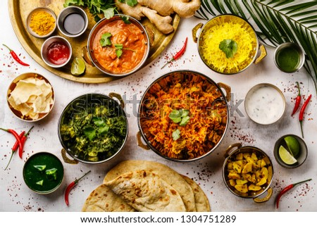 Indian food Curry butter chicken, Palak Paneer, Chiken Tikka, Biryani, Papad, Dal, Rice with Saffron and Naan bread on white background #1304751289