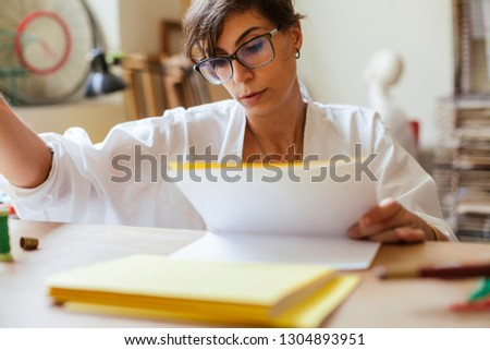 Young adult woman making a notebook in his laboratory #1304893951