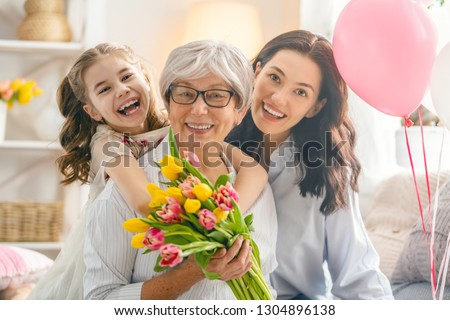 Happy women's day! Child daughter is congratulating mom and granny giving them flowers tulips. Grandma, mum and girl smiling and hugging. Family holiday and togetherness. #1304896138