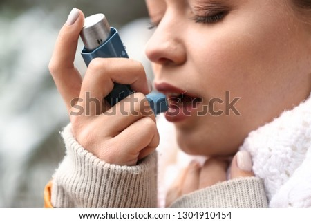 Young woman with inhaler having asthma attack outdoors, closeup Royalty-Free Stock Photo #1304910454