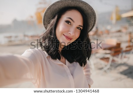 Charming brunette young woman expressing positive emotions during photoshoot at embankment. Elegant black-haired girl in gray hat making selfie with gently smile.