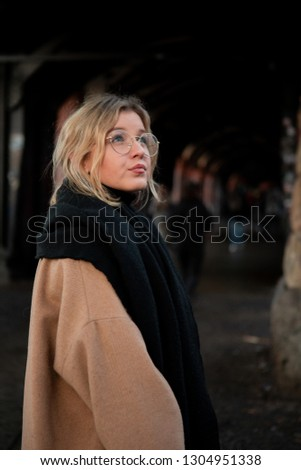 Close-up portrait of cheerful white woman in glasses on dark background. Photo of fashionable girl with blonde hair looking up. The model admires the city. #1304951338