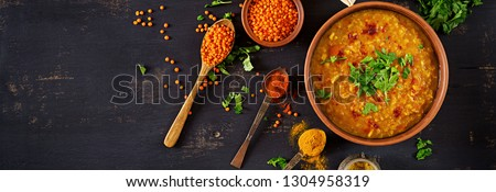 Indian dal. Food. Traditional Indian soup lentils.  Indian Dhal spicy curry in bowl, spices, herbs, rustic black wooden background. Top view. Authentic Indian dish. Overhead. Banner #1304958319