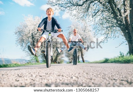 Father and son having fun spreading wide legs and screaming when riding bicycles on country road under blossom trees. Healthy sporty lifestyle concept image. #1305068257