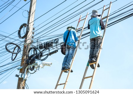 Electrician climbing the bamboo ladder to repair electric wires. #1305091624