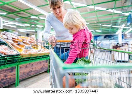 Mother having her toddler girl riding in shopping card of supermarket #1305097447
