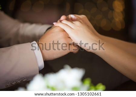 Close up side view of man and woman holding hands while sitting at wooden table in front of each other. Female and male hands of bride and groom on wedding day. Horizontal color photography. #1305102661