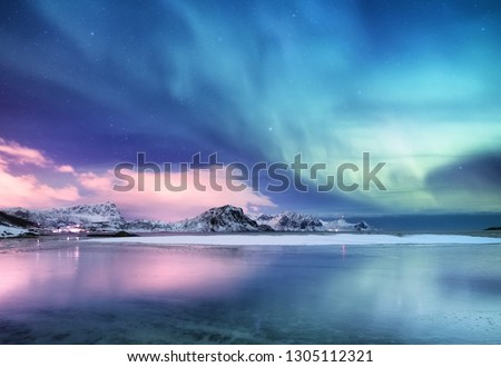 Aurora borealis on the Lofoten islands, Norway. Green northern lights above ocean. Night sky with polar lights. Night winter landscape with aurora and reflection on the water surface. Norway-image #1305112321