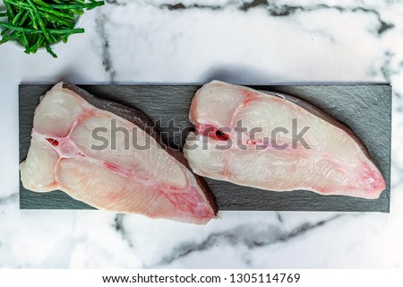 Two raw halibut steaks garnished with samphire - top view