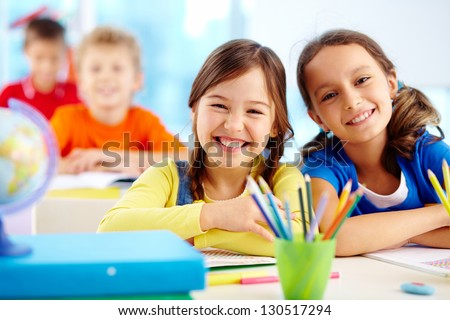 Portrait of two diligent girls looking at camera at workplace with schoolboys on background Royalty-Free Stock Photo #130517294