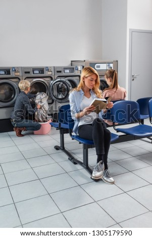 woman reading a book while senior woman washing clothes at laundromat #1305179590