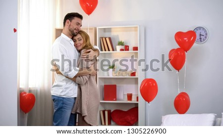 Husband tenderly hugging wife in room with heart-shaped balloons, romantic #1305226900