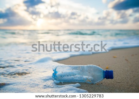 Used plastic water bottle washed up on the shore of a tropical beach, highlighting the worldwide crisis of plastic pollution on even the most remote islands Royalty-Free Stock Photo #1305229783