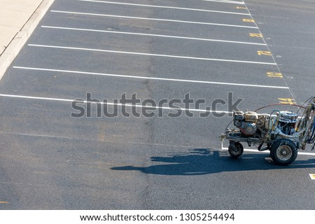 Worker with a striping mashing painting fresh lines in development parking lot, USA Royalty-Free Stock Photo #1305254494