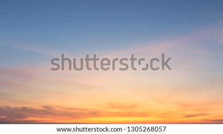 Beautiful sky painted by the sun leaving bright golden shades.Dense clouds in twilight sky in winter evening.Image of cloud sky on evening time.Evening sky scene with golden light from the setting sun #1305268057