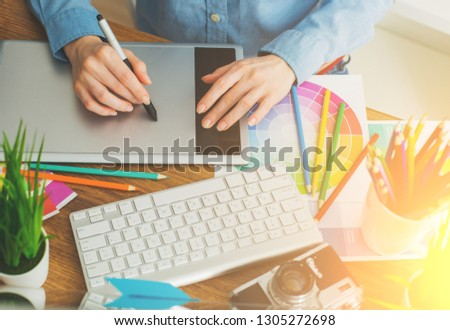 Young cute Graphic designer using graphics tablet to do his work at desk view from above #1305272698