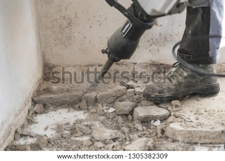 Construction worker on construction site with demolition hammer - chiseling close-up Royalty-Free Stock Photo #1305382309