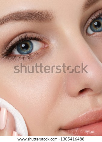 Portrait of young beautiful woman cleaning makeup from her face with cosmetic pad. Cleaning face, perfect skin, skincare and cosmetology concept. Extreme closeup, partial face view #1305416488