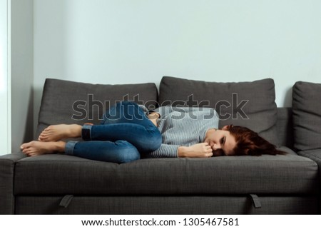 Young, beautiful girl suffers from stomach cramps and abdominal pain, lying on a home sofa. The concept of abdominal pain, female menstruation, stomach cramps. #1305467581