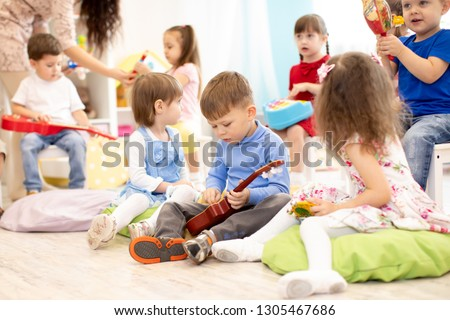 Group of kids playing musical toys. Early musical education in kindergarten or primary school #1305467686