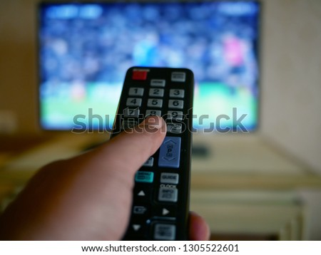 closeup of hand with the remote control television and presses the button.  #1305522601