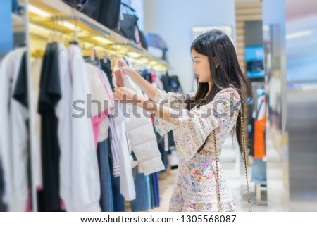 retail shopping concept, Beautiful Asian Thai girl chooses clothes in a shopping mall, Brown hair Smiling women Trying on a blouse, she is very happy after work in the business park near her office    #1305568087