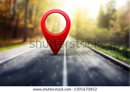 Red GPS pin on asphalt road and beauty autumn nature #1305670852