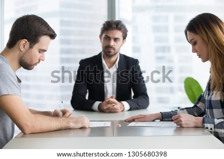 Spouses couple signing decree papers getting divorced in lawyers office, unhappy married family split break up end relationships giving permission to marriage dissolution and legal separation concept #1305680398