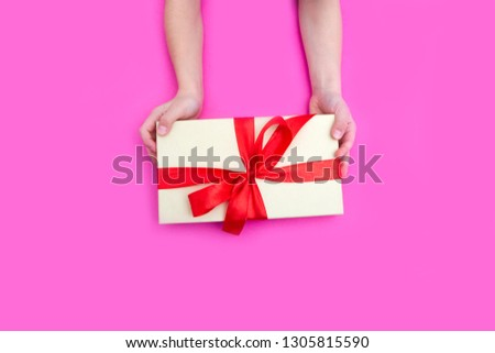 Children's hands hold gift box on a pink background. A concept by the Mother's Day. Vintage toning. Father's day. Birthday. #1305815590