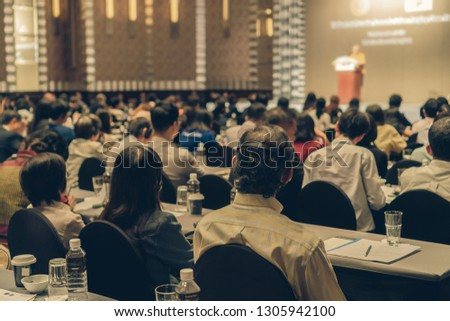 Rear view of Audience wearing and listening Speakers via Interpreter Headset on the stage in the conference hall or seminar meeting, business and education about investment concept Royalty-Free Stock Photo #1305942100