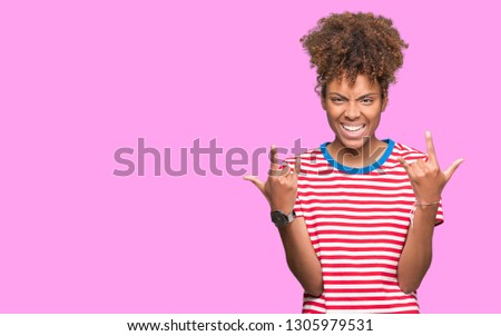 Beautiful young african american woman over isolated background shouting with crazy expression doing rock symbol with hands up. Music star. Heavy concept. #1305979531