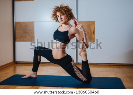 Sporty beautiful young woman practicing yoga, doing Splits Exercise, Monkey God Pose, stretching the thighs, hamstrings, groins, working out wearing black sport #1306050460