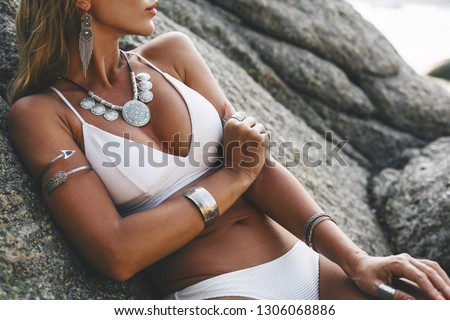 Photo of beautiful boho styled model wearing white swimsuit and silver bohemian jewelery on the beach in sunset #1306068886