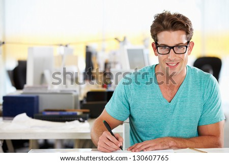 Man Writing At Desk In Busy Creative Office #130607765
