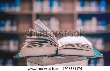 Stack of books in the library and blur bookshelf background #1306361674