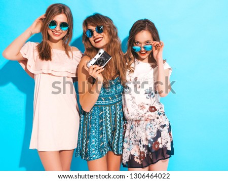 Three young beautiful smiling hipster girls in trendy summer casual dresses. Sexy carefree women posing near blue wall in round sunglasses. Taking pictures on retro camera #1306464022