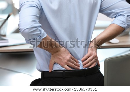 Businessman suffering from back pain at workplace, closeup Royalty-Free Stock Photo #1306570351