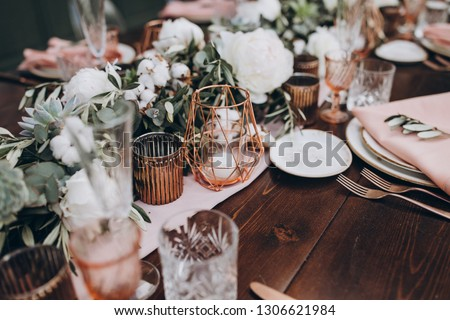 on wooden banquet table are glasses, plates, candles, table is decorated with compositions of cotton and eucalyptus branches, plates are decorated with napkins and sprig of Italian greenery Royalty-Free Stock Photo #1306621984