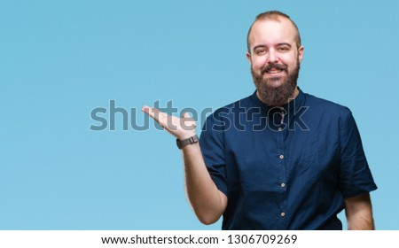 Young caucasian hipster man over isolated background smiling cheerful presenting and pointing with palm of hand looking at the camera. #1306709269