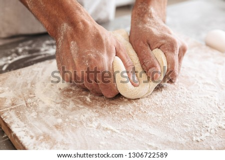 Closeup portrait of handsome male hands making dough for bread on table at bakery or kitchen #1306722589